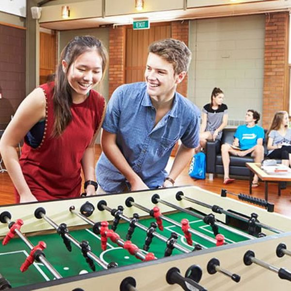 male_female_smiling_playing_foosball_student_life_INT_feature